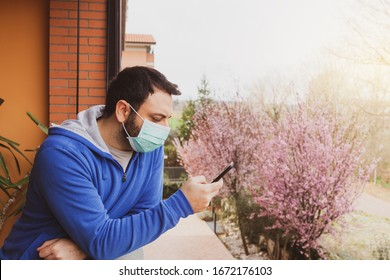 Young caucasian man with mask looking out to home terrace using mobile phone during quarantine due to coronavirus covid19 pandemic.