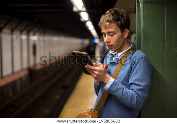 Young caucasian man in New York City subway station platform using tablet pc computer