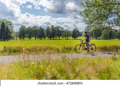 Young caucasian man on electric bike is watching countryside meadows