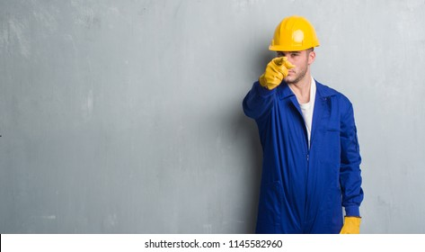 Young caucasian man over grey grunge wall wearing contractor uniform and safety helmet pointing with finger to the camera and to you, hand sign, positive and confident gesture from the front
