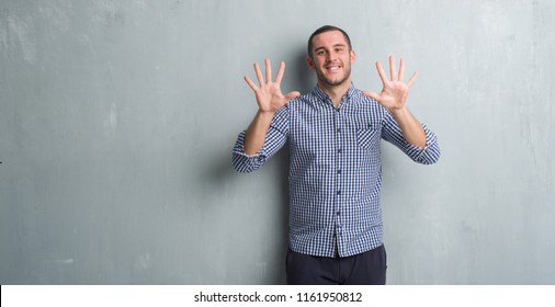 Young caucasian man over grey grunge wall showing and pointing up with fingers number ten while smiling confident and happy.