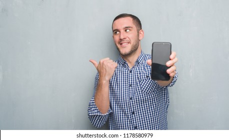 Young caucasian man over grey grunge wall showing blank screen of smartphone pointing and showing with thumb up to the side with happy face smiling