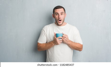 Young caucasian man over grey grunge wall driking a cup of coffee scared in shock with a surprise face, afraid and excited with fear expression