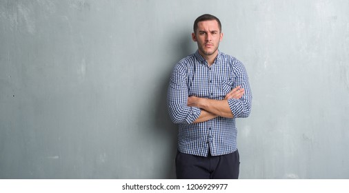 Young caucasian man over grey grunge wall skeptic and nervous, disapproving expression on face with crossed arms. Negative person.