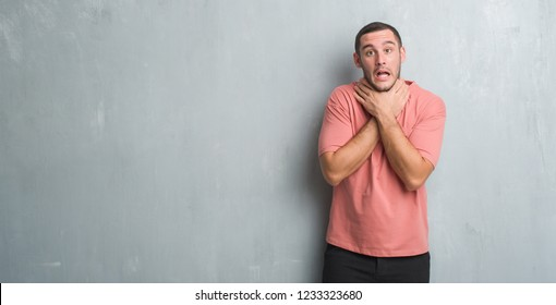Young caucasian man over grey grunge wall shouting and suffocate because painful strangle. Health problem. Asphyxiate and suicide concept.