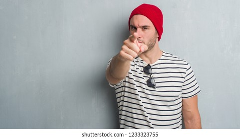 Young caucasian man over grey grunge wall wearing wool cap pointing with finger to the camera and to you, hand sign, positive and confident gesture from the front