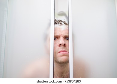 A young caucasian man peeks out of shower in soap. He is afraid that somebody looks on him and frowns his face