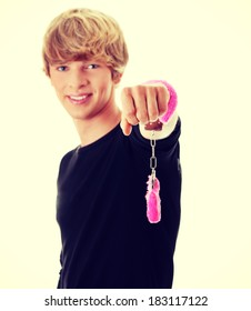 Young caucasian man with pink handcuff