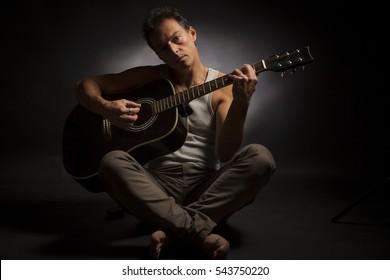 Young caucasian man play a acoustic guitar. Low key studio portrait