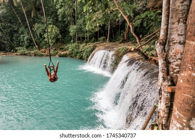A young caucasian man plays with a rope swing over the Cambugahay Falls in Siquijor Island, Philippines