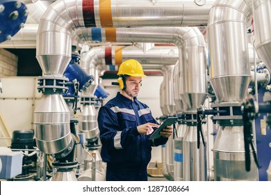 Young Caucasian man in protective suit using tablet while standing in heating plant.