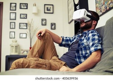 Young Caucasian man resting on comfortable sofa wearing VR headset glasses
