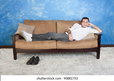 Young Caucasian man rests on sofa with shoes on floor