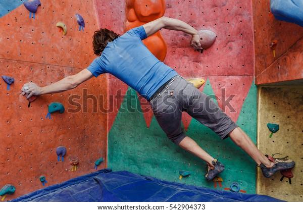 young caucasian man rock climbing indoors
