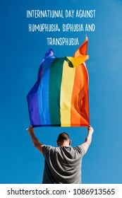a young caucasian man seen from behind holding a rainbow flag over his head against the blue sky