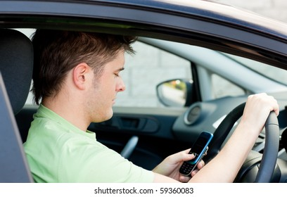 Young caucasian man sending a text while driving a car to work