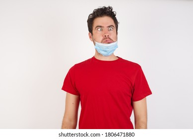 Young caucasian man with short hair wearing medical mask standing over isolated white background  making grimace and crazy face, screaming out of control, funny lunatic expressing freedom and wild.