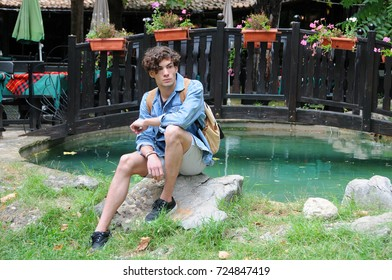 Young Caucasian man sits on the stone in the park