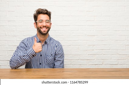 Young caucasian man sitting cheerful and excited, smiling and raising her thumb up, concept of success and approval, ok gesture