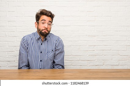 Young caucasian man sitting doubting and shrugging shoulders, concept of indecision and insecurity, uncertain about something