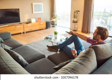 Young caucasian man sitting in his amazing modern apartment's living room, watching TV and changing the channel with the remote he is holding in his hands.