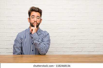 Young caucasian man sitting keeping a secret or asking for silence, serious face, obedience concept