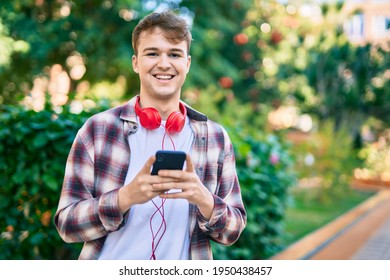 Young caucasian man smiling happy using smartphone and headphones at the park.