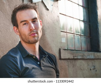 Young caucasian man with a solemn or serious facial expression looking into the lens.