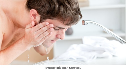 Young caucasian man spraying water on his face after shaving in the bathroom at home