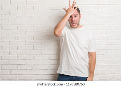 Young caucasian man standing over white brick wall surprised with hand on head for mistake, remember error. Forgot, bad memory concept.