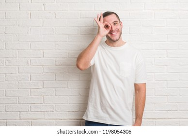 Young caucasian man standing over white brick wall doing ok gesture shocked with surprised face, eye looking through fingers. Unbelieving expression.