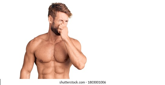 Young caucasian man standing shirtless smelling something stinky and disgusting, intolerable smell, holding breath with fingers on nose. bad smell