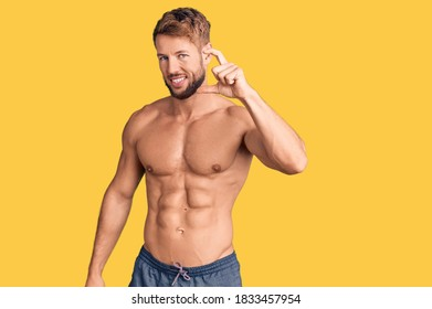Young caucasian man standing shirtless smiling and confident gesturing with hand doing small size sign with fingers looking and the camera. measure concept.
