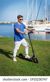 Young Caucasian man stays with an electric scooter on grass near the sea in the marina