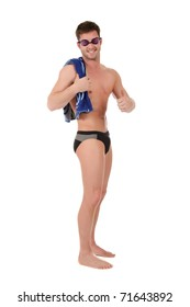 Young caucasian man swimmer with goggles and towel on shoulder. Smiling guy with thumb up. Studio shot. White background