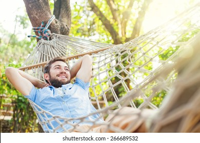 young caucasian man swinging in a hammock in a pleasant laziness of a weekend morning. He is smiling through his beard