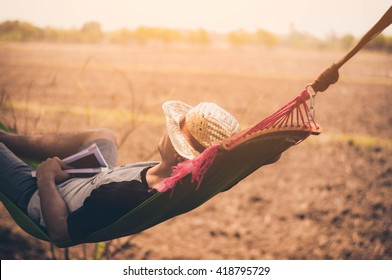 young caucasian man swinging in a hammock in a pleasant laziness
