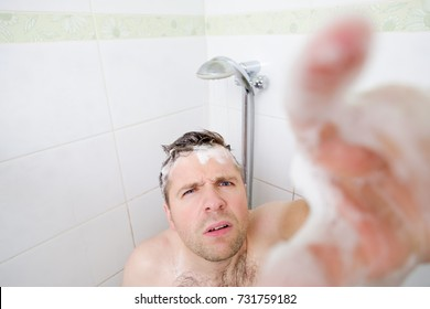 A young caucasian man takes a shower and notices a hidden camera. He stretches his hand forward with a suspicious look up. The concept of interference in privacy and spying.