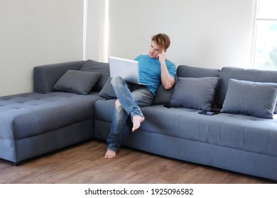 Young Caucasian man is thinking and searching online social media with laptop. He is sitting on sofa in living room. Work from home for Covod-19 outbreak. Lifestyle and techonology on holiday C
