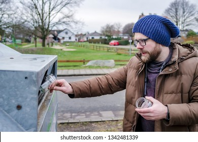 Young caucasian man throws out used white glass jars from canned baby food into a recycling container in a provincial European city.