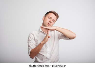 Young caucasian man tired and bored, making a timeout gesture. He needs some rest because of work stress
