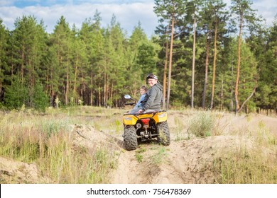 A young caucasian man and a toddler boy riding an ATV quad bike over rough terrain near pine forest. Family sport activity concept.