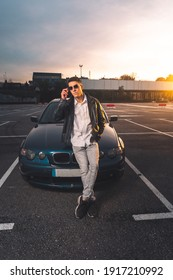 Young caucasian man using a smartphone with a sports car behind