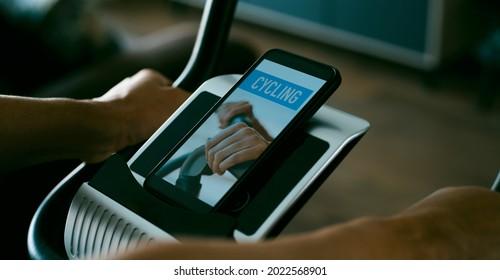 joven caucásico usando una bicicleta estática en su sala de estar mientras mira su smartphone, que lee ciclismo en su pantalla, en formato panorámico para usar como banner web o cabecera