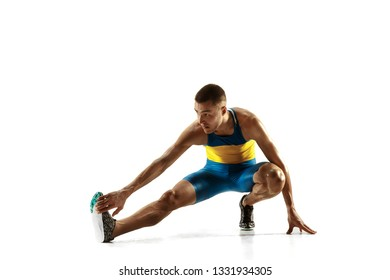 Young caucasian man warming up before run isolated on white studio background. One male runner or jogger. Silhouette of stretching athlete with shadows.