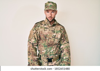 Young caucasian man wearing camouflage army uniform looking sleepy and tired, exhausted for fatigue and hangover, lazy eyes in the morning.