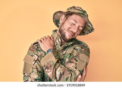 Young caucasian man wearing camouflage army uniform hugging oneself happy and positive, smiling confident. self love and self care