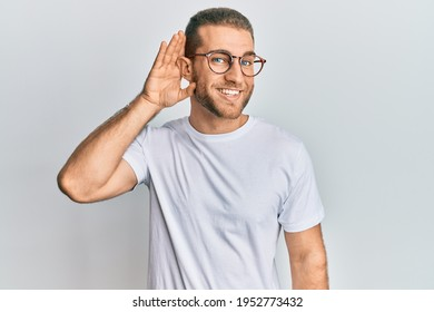 Young caucasian man wearing casual clothes and glasses smiling with hand over ear listening an hearing to rumor or gossip. deafness concept.