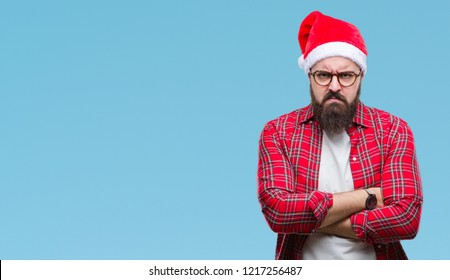 Young caucasian man wearing christmas hat over isolated background skeptic and nervous, disapproving expression on face with crossed arms. Negative person.