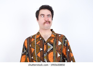Young caucasian man wearing generic pattern printed shirt against yellow wall making grimace and crazy face, screaming out of control, funny lunatic expressing freedom and wild.